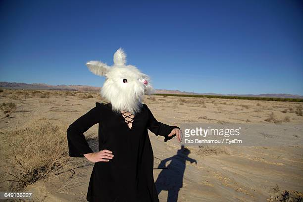 woman wearing rabbit mask at field against clear blue sky - rabbit mask stock pictures, royalty-free photos & images