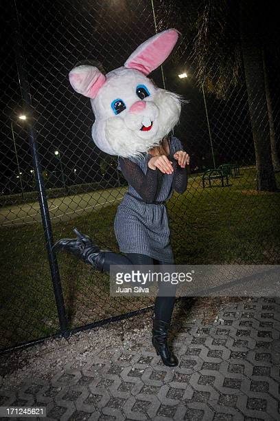 Woman wearing rabbit mask in the street at night
