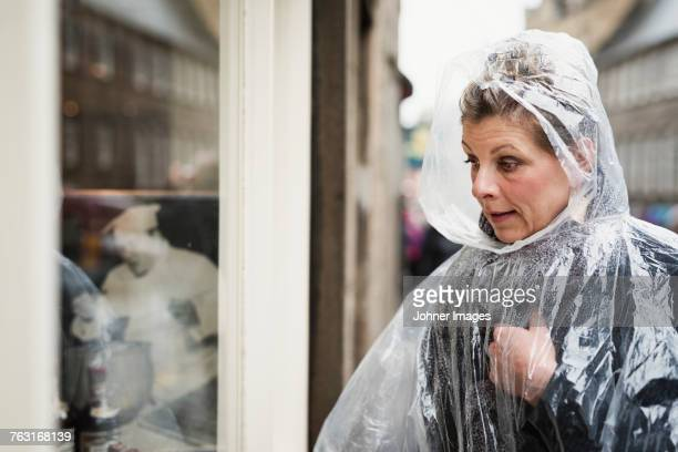 woman wearing rain poncho - shop window stock pictures, royalty-free photos & images