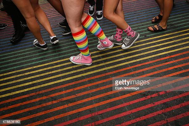 A woman wearing rainbowcolored socks walks across a rainbowcolored crosswalk during a gay pride celebration in San Francisco's famous Castro...