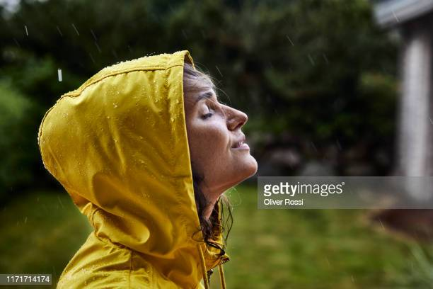 woman wearing raincoat during heavy rain in garden - sensory perception stock pictures, royalty-free photos & images