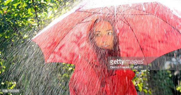 Woman Wearing Raincoat With Umbrella Standing Under Rain At Yard