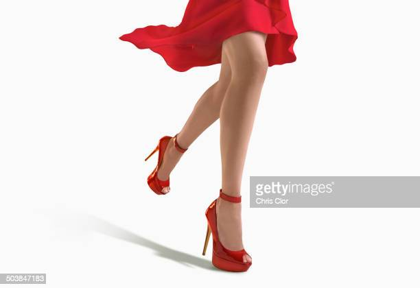 woman wearing red dress and heels - red dress stock photos and pictures