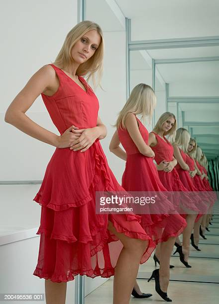 Woman wearing red dress, looking at reflection in mirror