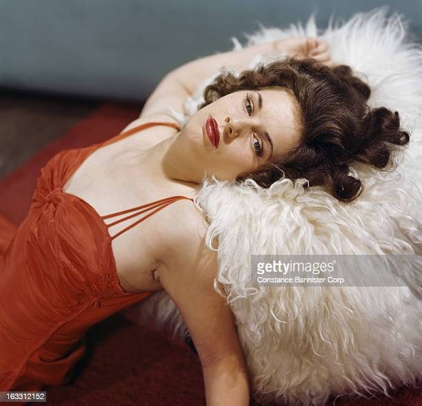 Woman wearing red dress lying back on a white fur New York City USA