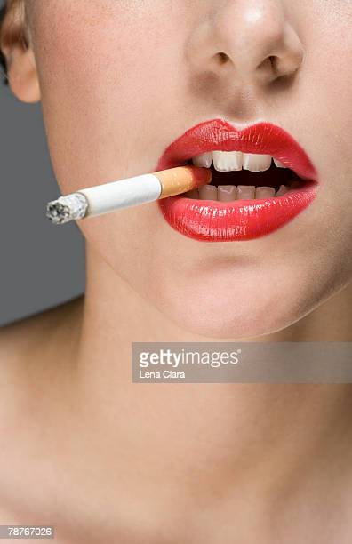 A woman wearing red lipstick and smoking a cigarette