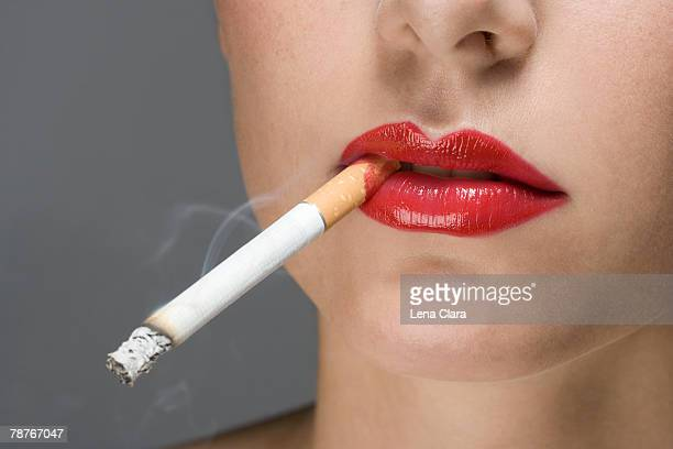 a woman wearing red lipstick and smoking a cigarette - beautiful women smoking cigarettes stock photos and pictures