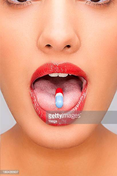 Woman wearing red lipstick with pill on tongue