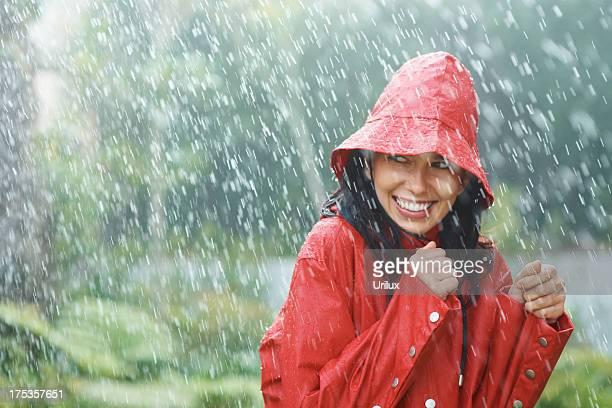 Woman wearing red rain coat in the rain