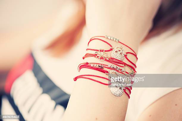 woman wearing red string bracelets with charm