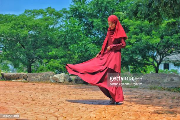 Woman Wearing Red Traditional Clothing While Standing Against Trees
