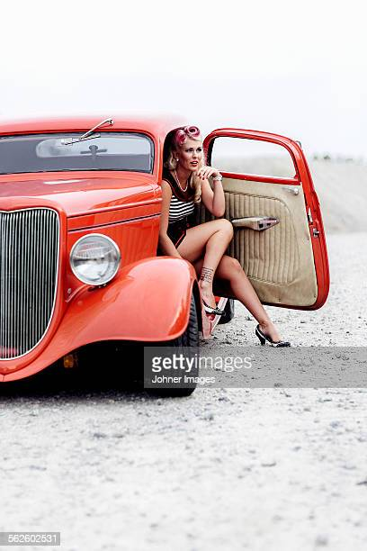 woman wearing retro clothes sitting in vintage car - rockabilly photos et images de collection