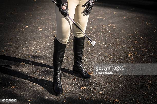 woman wearing riding boots, holding riding crop, low section - riding crop stock photos and pictures