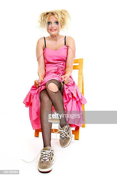 woman wearing ripped tights and prom dress sitting in chair - bizarre fashion stock pictures, royalty-free photos & images