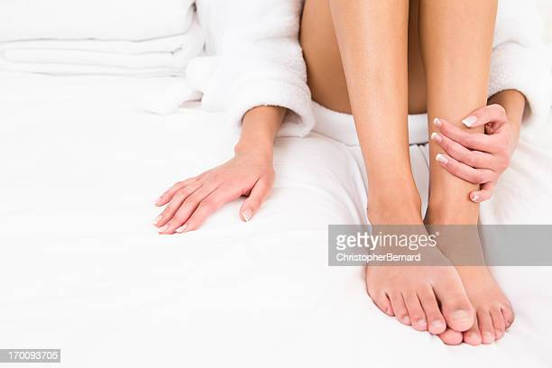 Woman wearing robe sitting on bed