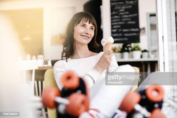 woman wearing roller skates sitting in a cafe, eating icecream - ijs of rolschaatsen stockfoto's en -beelden
