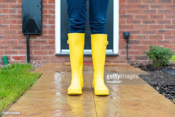 woman wearing rubber boot standing in back yard during rainy season - gummistiefel frau stock-fotos und bilder