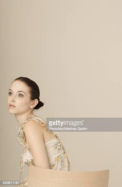 Woman wearing ruffly dress, hair in bun, portrait