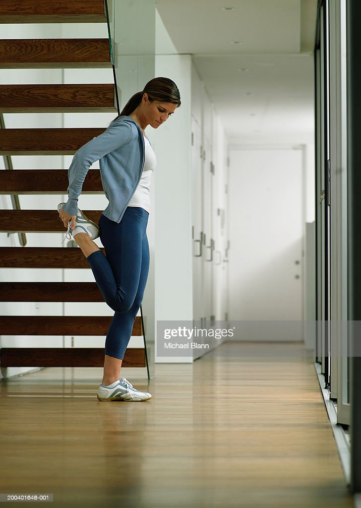 Woman wearing running clothes performing leg stretch by stairs : Stock Photo