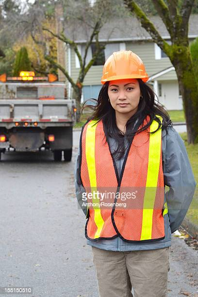 Woman wearing safety gear with truck in the background