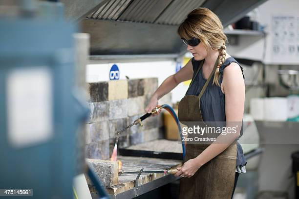 Woman wearing safety goggles using blowtorch for metalworking