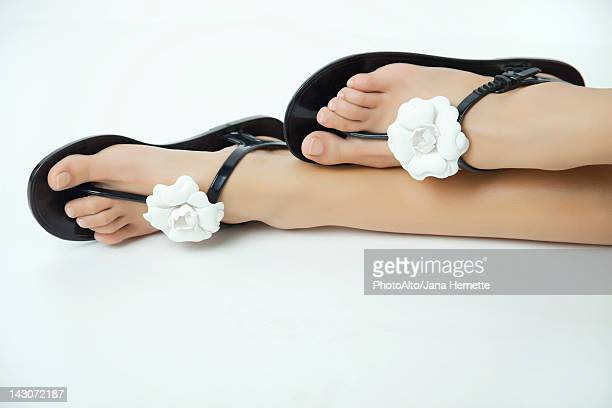 Woman wearing sandals decorated with flowers, cropped