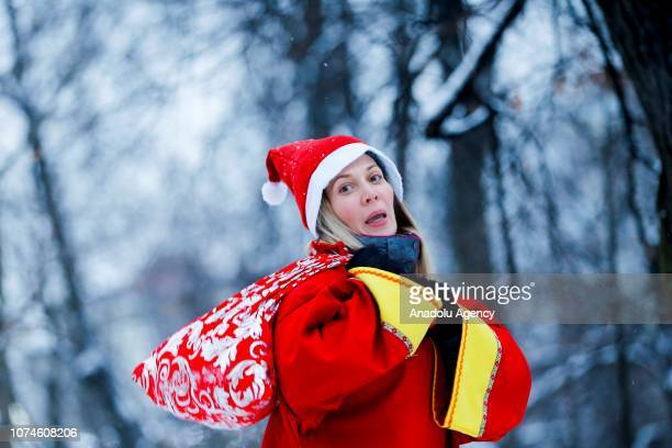 A woman wearing Santa Claus costume enjoys the Winter holiday 'Moscow longevity' Festival at the Sokolniki Park exhibition center in Moscow Russia on...