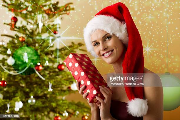 Woman wearing Santa hat and holding Christmas present, portrait