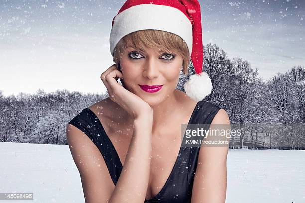 Woman wearing Santa hat in snow