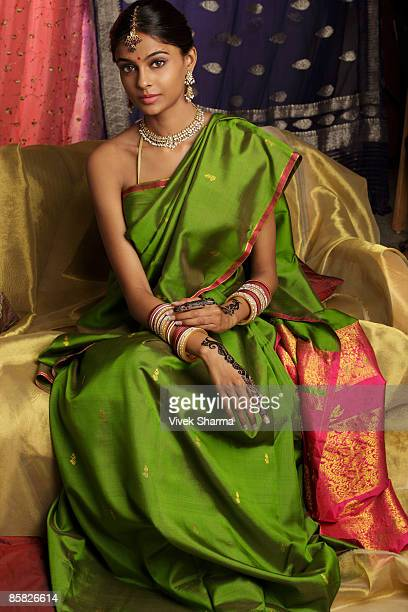 woman wearing sari, surrounded by sari fabric, decorated with henna tattoos, jewelry and bindi - sari stock pictures, royalty-free photos & images