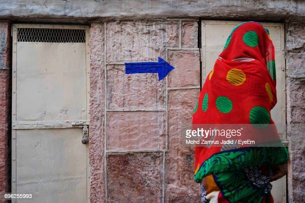 Woman Wearing Sari Walking Against Arrow Sign On Wall