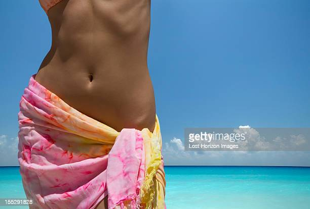 woman wearing sarong on beach - sarong stock photos and pictures