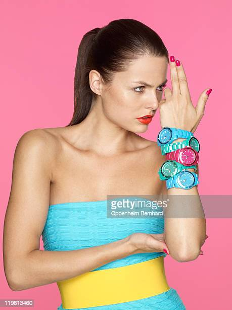 Woman wearing several watches making gun shapes