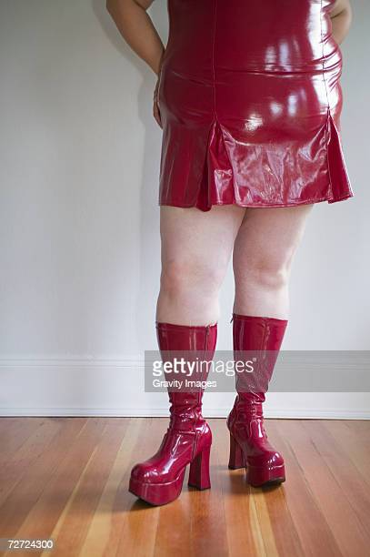 Woman wearing shiny red dress and high heeled boots, low section