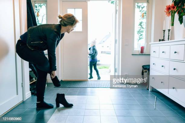 woman wearing shoes while daughter walking out of doorway - women trying on shoes stock pictures, royalty-free photos & images