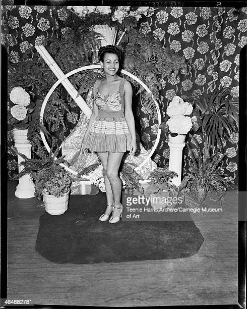 Woman wearing short sundress standing against backdrop of floral curtain ferns and hydrangeas for Beauty Shop Owners' Fashion Review in Schenley High...