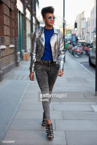Woman wearing silver jacket and sunglasses walking in street
