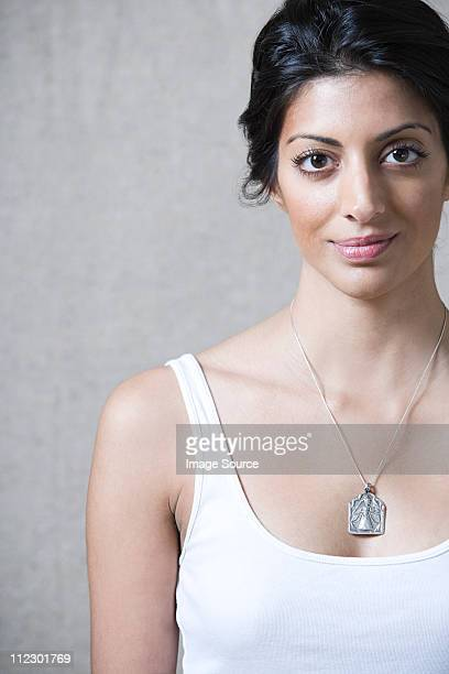 Woman wearing silver pendant looking at camera