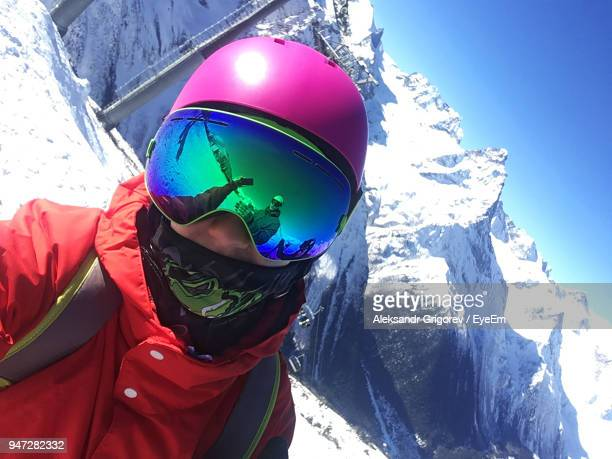 woman wearing ski goggles against mountains during winter - ski goggles stock pictures, royalty-free photos & images