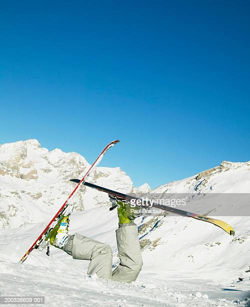 woman wearing skis buried in snow, legs in air - ski humour photos et images de collection