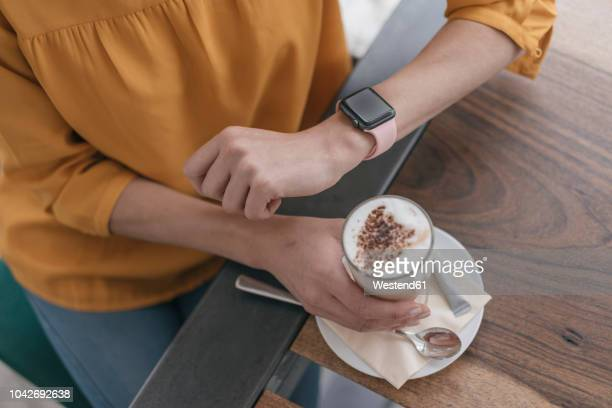 woman wearing smartwatch, sitting in cafe, drinking coffee - tijdmeter stockfoto's en -beelden