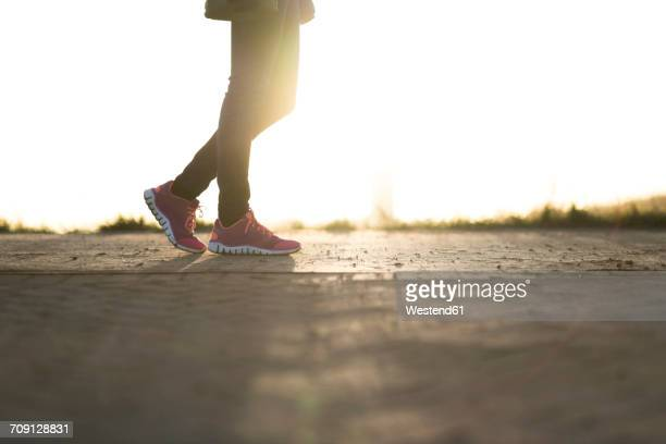 Woman wearing sneakers strolling at sunset, partial view