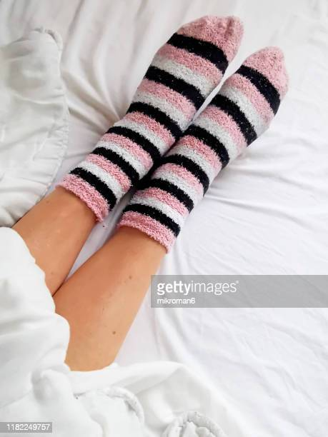 woman wearing socks on bed - bed stock pictures, royalty-free photos & images