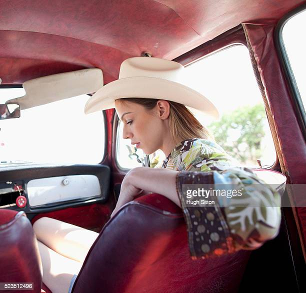 woman wearing sombrero sitting in old car - hugh sitton stock pictures, royalty-free photos & images