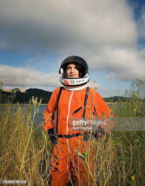 Woman wearing space suit and helmet, smiling