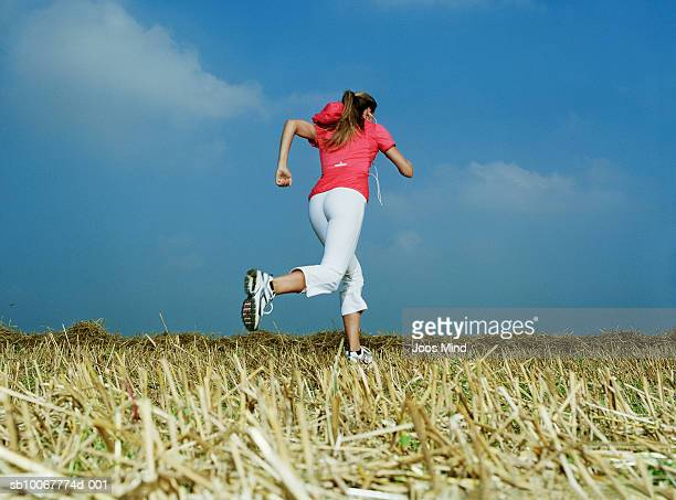 woman wearing sports clothes running in field, rear view - joggeuse photos et images de collection