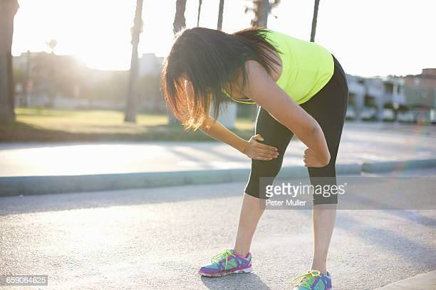 woman wearing sports clothing hands on knees bending forward - older woman bending over stock pictures, royalty-free photos & images