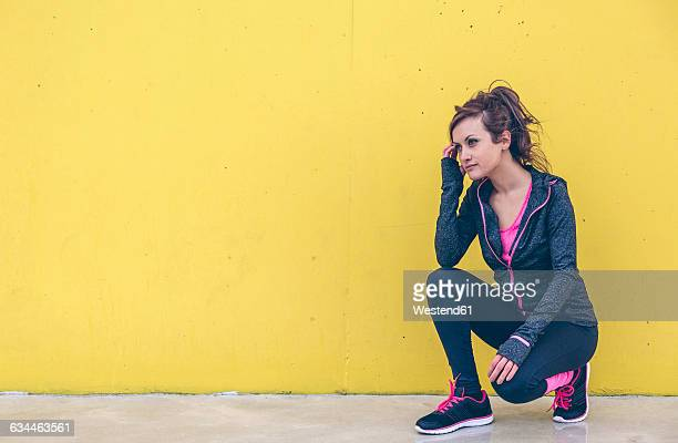 Woman wearing sports wear crouching in front of yellow wall
