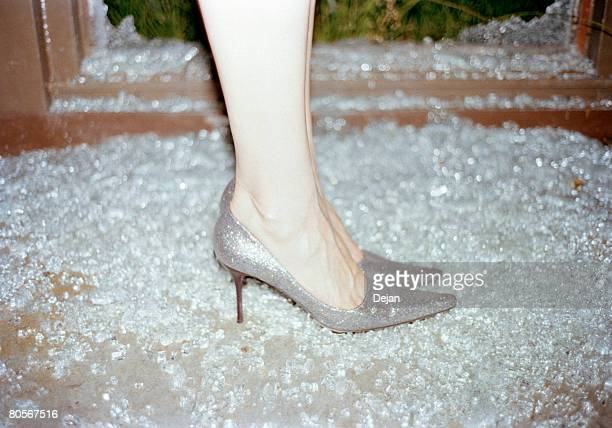 A woman wearing stilettos standing in broken glass