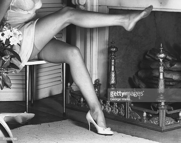 woman wearing stockings sitting by fireplace, (b&w), low section - stockings no shoes stock pictures, royalty-free photos & images